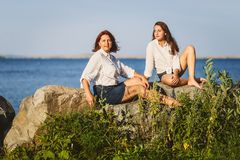 Two women sit on the rocks on the coast in the summer stock images