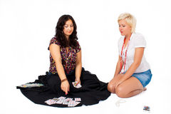 Two women sit and tell fortune. On a white background Stock Photo