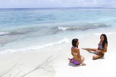 Two women sitting on beach Stock Images