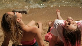 Two women sitting on beach in warm weather. stock footage