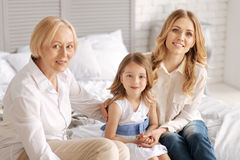 Two women sitting on bed with child in between Stock Photography