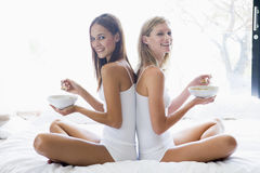 Two women sitting on bed eating cereal