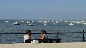 Two women sitting on bench talking (with sound). A view or scene on the water stock video footage