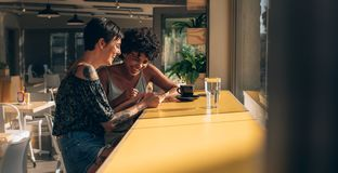 Friends engrossed in using a smart phone at cafe Royalty Free Stock Image