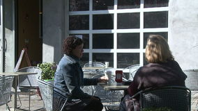 Two women sitting on a cafe patio talking (3 of 4) stock video