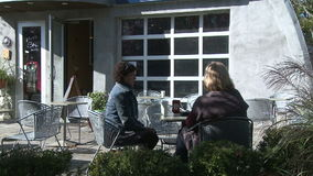 Two women sitting on a cafe patio talking (2 of 4) stock footage