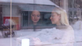 Two women sitting in cafe with phone. Two young friends rest in a cafe in the cold winter weather. Two women sitting in cafe with phone. View from the street stock video footage
