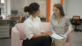 Two women sitting on the couch in the office talking and discussing the work schedules emotionally communicating and. Laughing, office workers explain to each stock footage