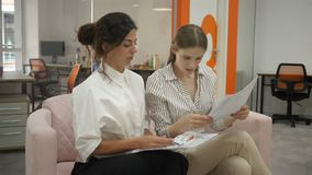 Two women sitting on the couch in the office talking, office workers two young women reading documents laughing, close. Up view of the side, documents stock footage