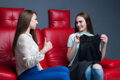 Two women sitting on couch and tries on dresses Royalty Free Stock Photography