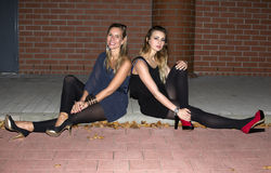 Two women sitting on a curb Stock Photos