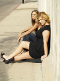 Two Women Sitting Curb Sidewalk Sunny Day Stock Image