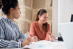 Two woman sitting at a desk and one is laughing royalty free stock image