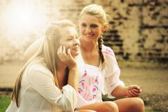 Two Women Sitting Down Smiling Stock Photo