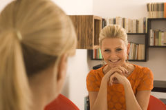 Two women sitting face to face Royalty Free Stock Photos
