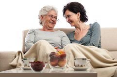 Two women sitting in front coffee table talking and laughing Royalty Free Stock Photos