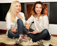 Two women sitting on the fur carpet at fireplace Royalty Free Stock Photos