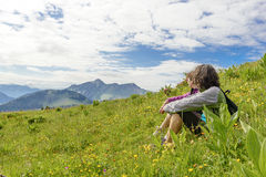 Two women sitting in the grass and looking at the landscape Royalty Free Stock Photo