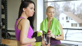 Two women are sitting in the gym near the big window and drinking water from the bottles. The brunette lady is wearing purple sportswear and her blond friend stock video footage