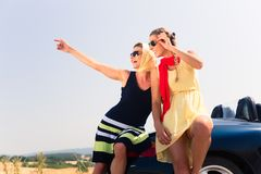 Two women sitting on hood of convertible car Royalty Free Stock Photography