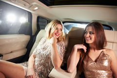Two women sitting in limo looking at each other, in-car view Stock Image
