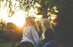 Two Women Sitting Near Green Tree during Sunset Royalty Free Stock Photos