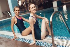 Two women sitting near the pool at the gym. They look happy, fashionable and fit. royalty free stock images