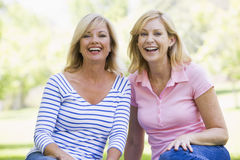 Two women sitting outdoors smiling Royalty Free Stock Image