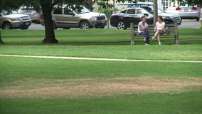 Two women sitting on a park bench stock footage
