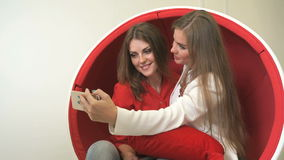 Two women sitting in red chair, making selfies. Attractive young women sitting in red chair, making selfies with mobile phone and waiting for dentist visit in stock footage