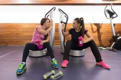 Two women sitting relaxing on device similar to. Power plate stock images