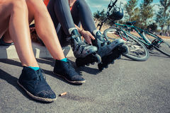 Two women sitting by roadside wearing rollerblades Royalty Free Stock Image