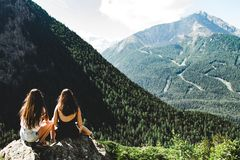 Two Women Sitting on Rock Facing Mountains Under White Cloudy Skies stock images