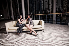 Two women sitting on sofa. Two young women sitting and talking on a sofa Royalty Free Stock Photography