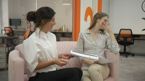 Two women sitting on sofa in office talking and discussing work schedules emotionally communicating and laughing, office