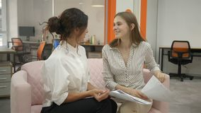 Two women sitting on a sofa in the office talking, office workers two young women laughing discussing office problems. Office, documents, securities hd stock footage