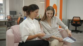 Two women sitting on sofa in office talking, office workers two young women reading documents laughing discussing. Schedules in documents, office, documents stock footage