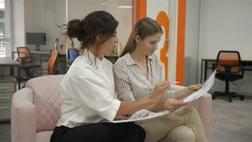 Two women sitting on a sofa in the office talking, one with women showing documents and they are discussing them. Together, close-up view of the side, office stock video