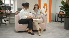 Two women sitting on a sofa in the office talking, one with women shows documents and they together discuss them. Informal situation, the subordinate shows stock video
