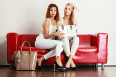 Two women sitting on sofa presenting bag Stock Photo