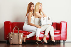 Two women sitting on sofa presenting bags Stock Images