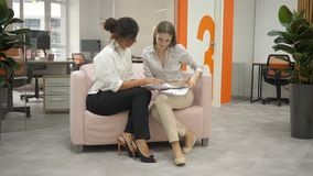 Two women sitting on a sofa talking in the office, one with women showing documents and they together condemn them. Office workers, office, documents stock footage