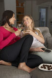 Two Women Sitting On Sofa Watching TV Drinking Wine Royalty Free Stock Photos