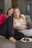 Two Women Sitting On Sofa Watching TV Drinking Wine Royalty Free Stock Photography