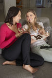 Two Women Sitting On Sofa Watching TV Drinking Wine Stock Images