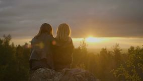 Two women are sitting on the stone. And looking on the sunset in the forest stock footage