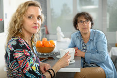 Two women sitting at table in kitchen and drinking coffee. Stock Photos