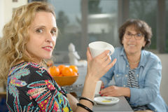 Two women sitting at table in kitchen and drinking coffee. Two women sitting at table in kitchen and drinking cup of coffee Stock Photos