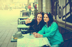 Two women sitting at a table on the street stock photos