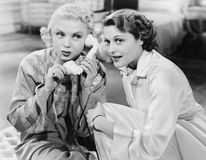 Two women sitting together and listening on the telephone receiver Stock Photo